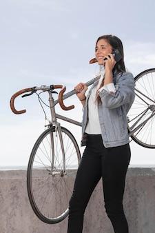 Mulher jovem falando ao telefone ao lado de uma bicicleta