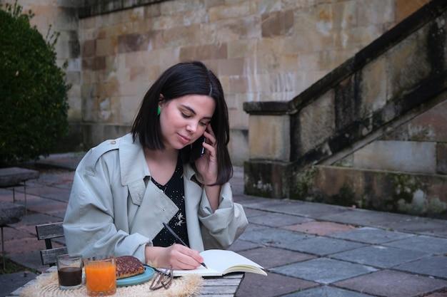 Mulher jovem falando ao telefone e escrevendo em um caderno enquanto toma café da manhã no terraço