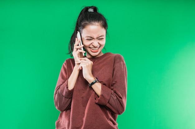Mulher jovem falando ao telefone e rindo alegremente com alguém contra um fundo verde