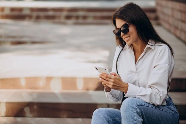 Mulher jovem falando ao telefone e sentada na escada