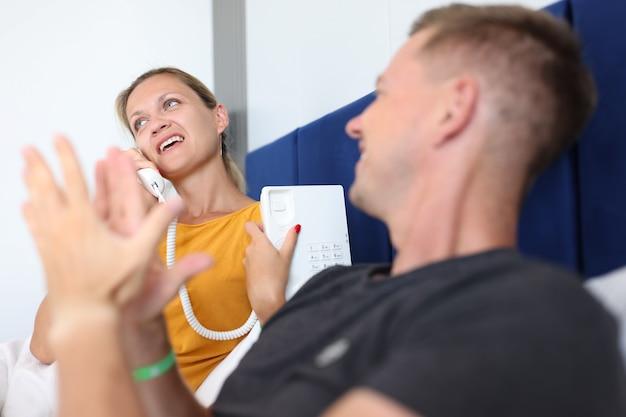 Mulher jovem falando ao telefone em quartos de hotel enquanto estava deitada na cama com um homem chamando um assistente para