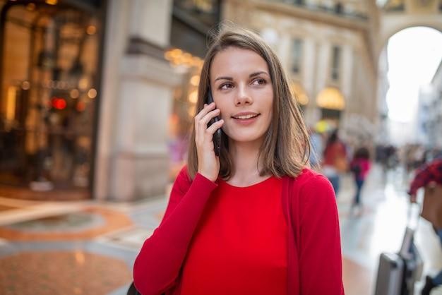 Mulher jovem falando ao telefone enquanto caminha pela cidade