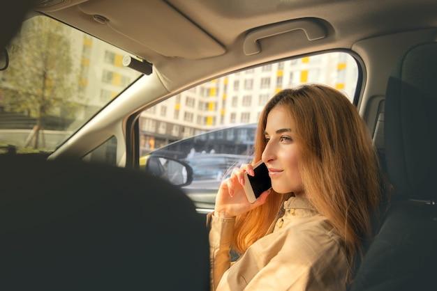 Mulher jovem falando ao telefone enquanto está sentada no banco do passageiro da frente do carro