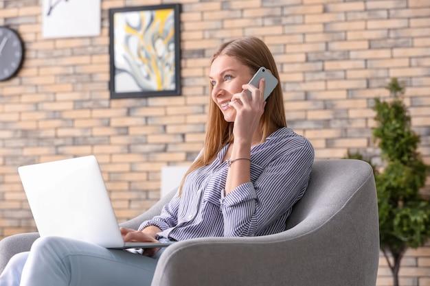 Mulher jovem falando ao telefone enquanto trabalha em um laptop em casa