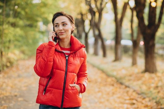 Mulher jovem falando ao telefone no parque outonal