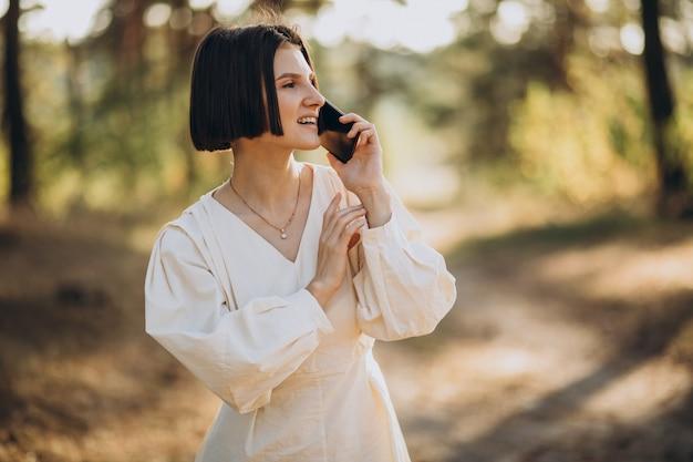Mulher jovem falando ao telefone no parque