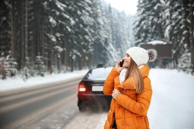 Mulher jovem falando ao telefone perto da estrada em resort de inverno