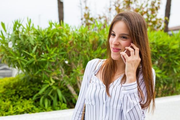 Mulher jovem, falando, com, telefone móvel, cidade