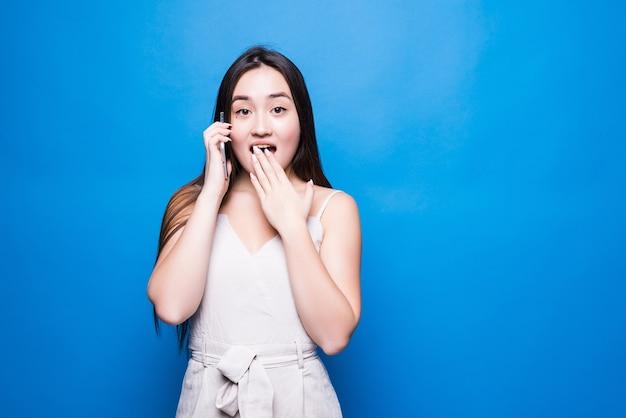 Mulher jovem falando em smartphone e expressando surpresa isolada sobre uma parede azul