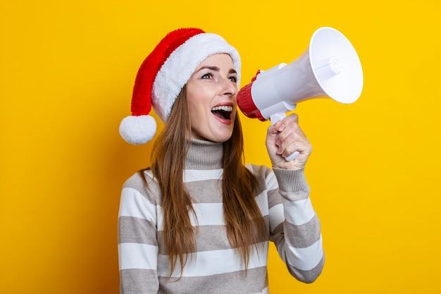 Mulher jovem falando em um megafone em um fundo amarelo.