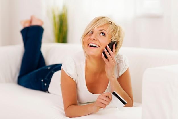 Mulher jovem falando no celular e segurando um cartão de crédito