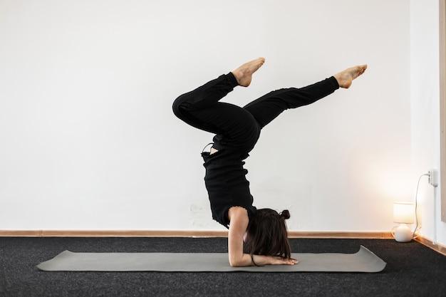Mulher jovem faz parada de mãos e mantém o equilíbrio em uma sala de ginástica. menina está em uma pose de ioga.