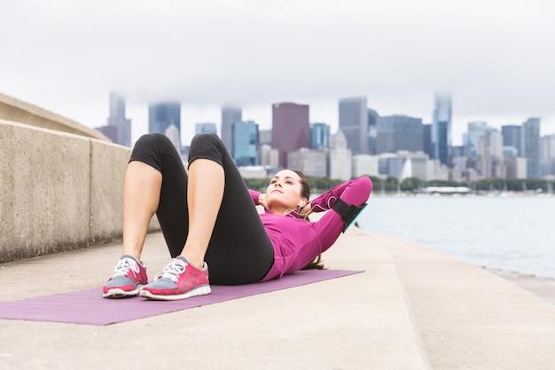 Mulher jovem, fazendo, abs, exercícios, com, chicago, skyline