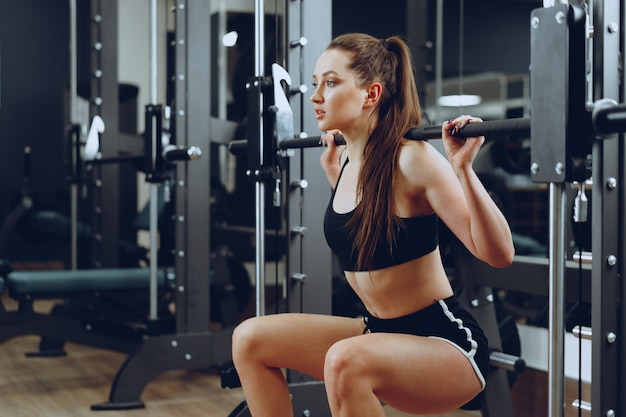 Mulher jovem fazendo agachamento com barra em um aparelho de ginástica