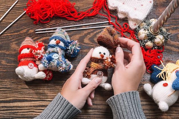Mulher jovem fazendo brinquedos de natal feitos à mão em uma mesa de madeira