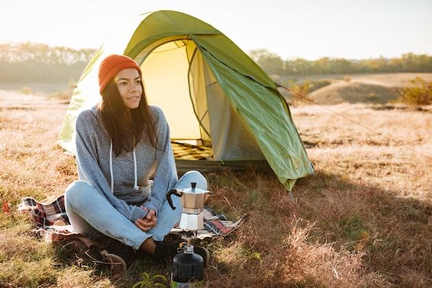 Mulher jovem fazendo café ao ar livre perto de uma tenda