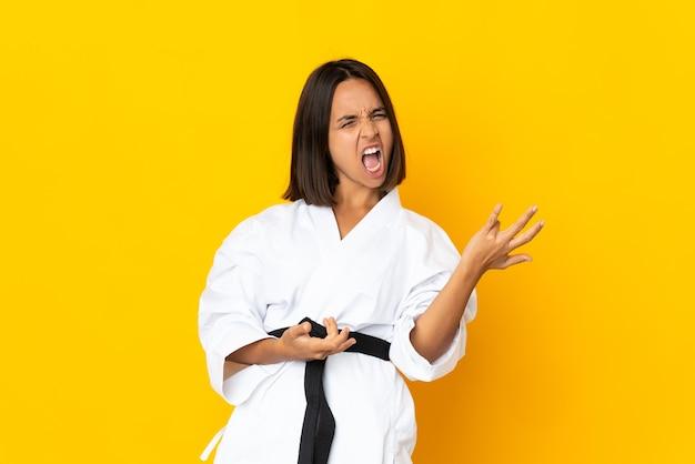 Mulher jovem fazendo caratê, isolada em um fundo amarelo fazendo gesto de guitarra