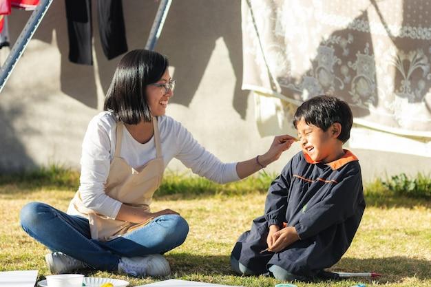 Mulher jovem fazendo cócegas em uma criança no quintal em um dia ensolarado com roupas caídas ao fundo