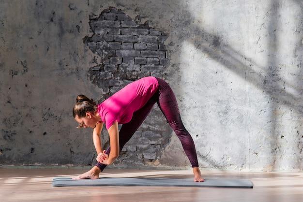 Mulher jovem, fazendo, esticando exercício, em, a, ioga, classe