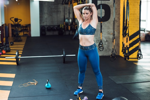 Mulher jovem, fazendo, esticando exercício, em, ginásio