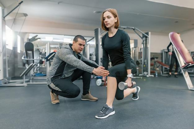 Mulher jovem, fazendo, exercícios, com, instrutor pessoal, em, ginásio