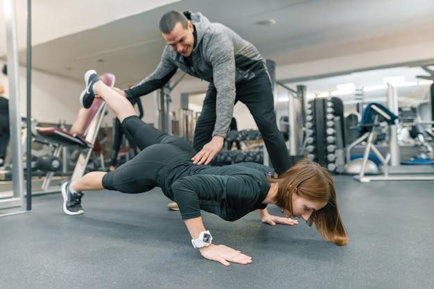 Mulher jovem, fazendo, exercícios, com, instrutor pessoal