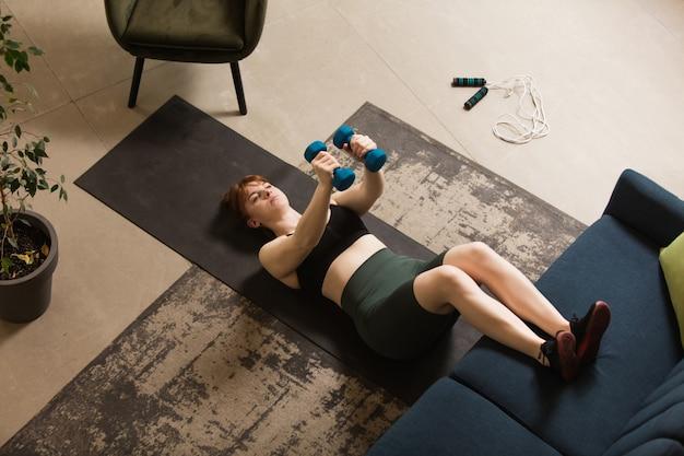 Mulher jovem fazendo exercícios de ioga aeróbica em casa estilo de vida esportivo ficando ativa durante o confinamento