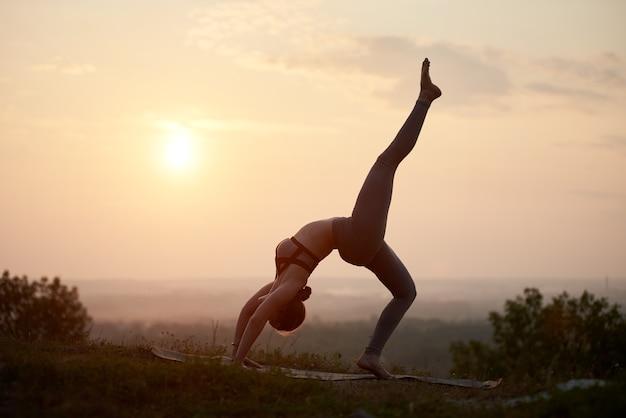 Mulher jovem fazendo exercícios de ioga ao ar livre ao pôr do sol