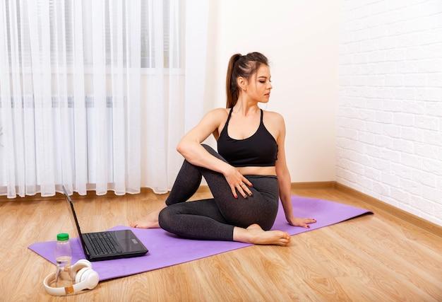 Mulher jovem fazendo exercícios de ioga dentro de casa, em casa, meditando