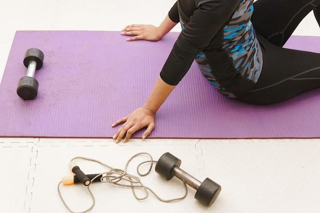Mulher jovem fazendo exercícios de ioga em casa, estilo de vida ficando ativa durante o confinamento