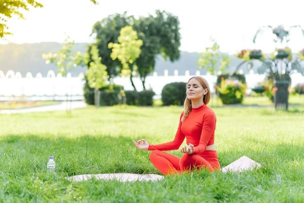 Mulher jovem fazendo exercícios de ioga em um parque verde