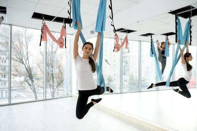 Mulher jovem fazendo exercícios de ioga voadora na academia