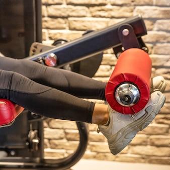 Mulher jovem fazendo exercícios de leg press na academia
