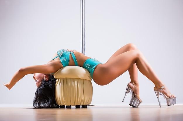Mulher jovem fazendo exercícios de pole dance isolado no fundo branco