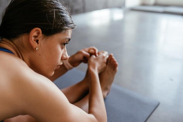 Mulher jovem fazendo exercícios de pose de ioga em casa, estilo de vida saudável