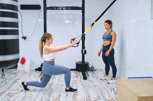 Mulher jovem fazendo exercícios de trx sob a supervisão de um personal trainer