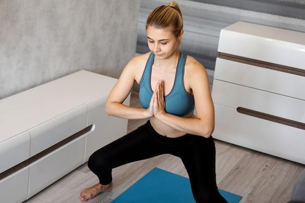 Mulher jovem fazendo exercícios e agachamentos na sala de estar de casa