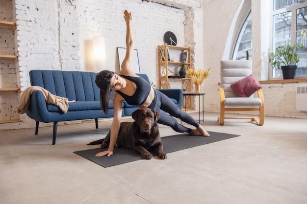 Mulher jovem fazendo exercícios em casa durante exercícios de ioga de bloqueio com o cachorro