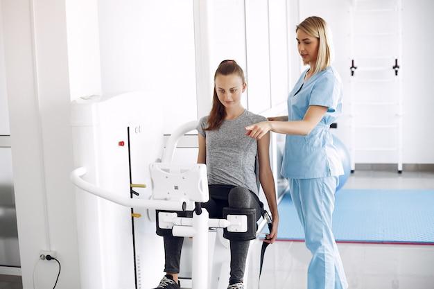 Mulher jovem fazendo exercícios no simulador com terapeuta na academia