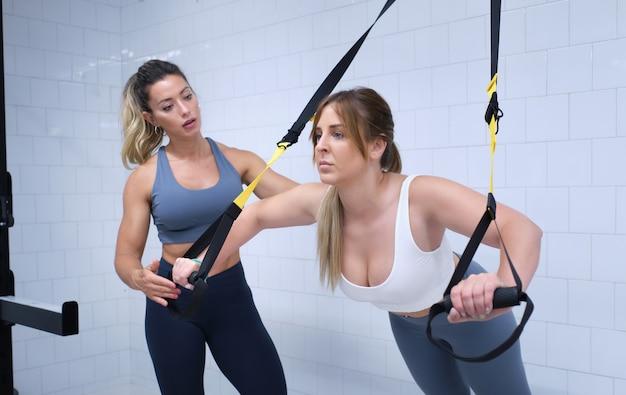 Mulher jovem fazendo exercícios trx em uma academia com um personal trainer