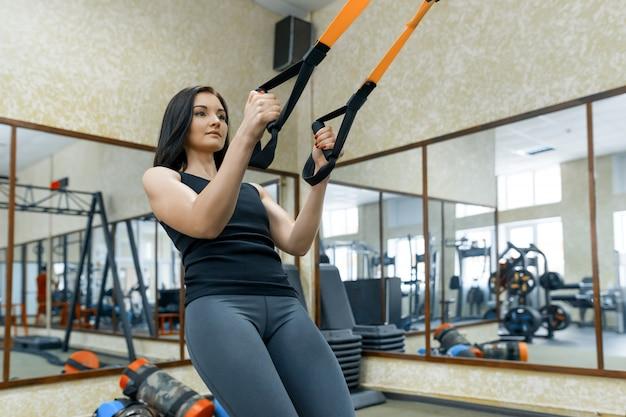 Mulher jovem, fazendo, exercícios, usando, a, correias, sistema