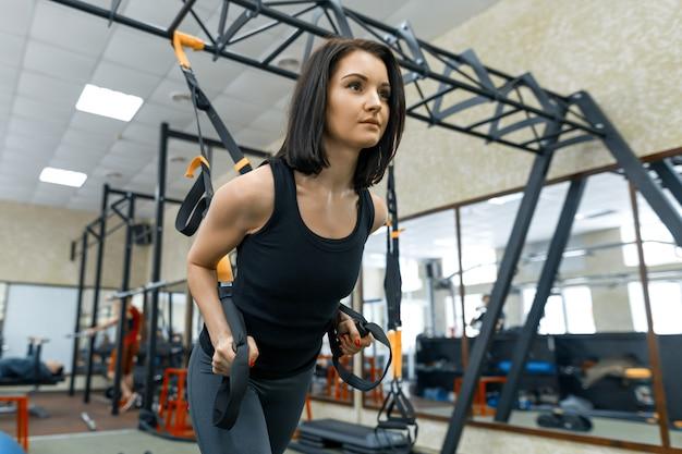 Mulher jovem, fazendo, exercícios, usando, a, trx, sistema
