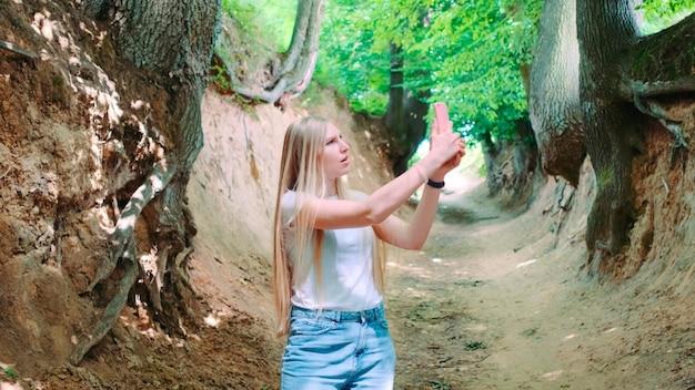 Mulher jovem fazendo fotos em um smartphone em um desfiladeiro mágico de raízes situado em kazimierz dolny, na polônia