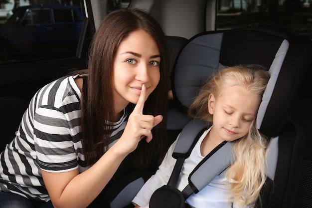 Mulher jovem fazendo gestos de silêncio perto da garota adormecida no carro