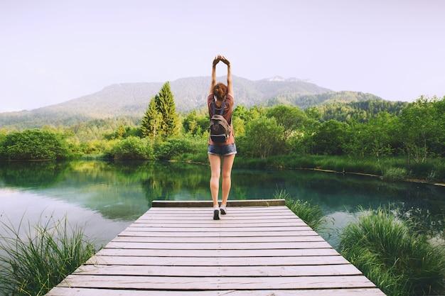 Mulher jovem fazendo ioga e meditando em posição de lótus no fundo da natureza