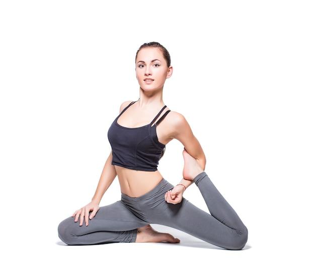 Mulher jovem fazendo ioga em fundo branco