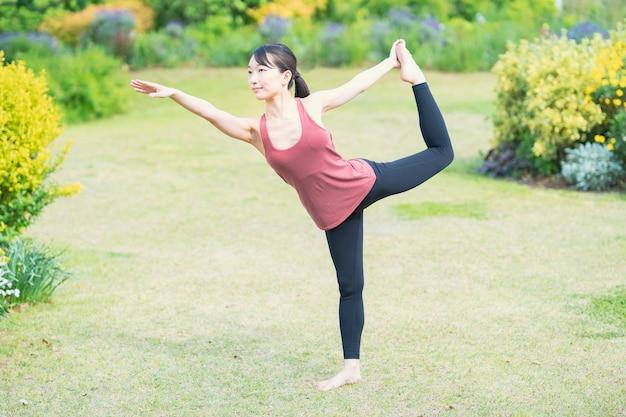 Mulher jovem fazendo ioga em um parque verde em um dia bom