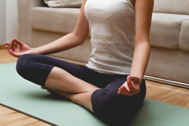 Mulher jovem fazendo ioga no tapete em casa