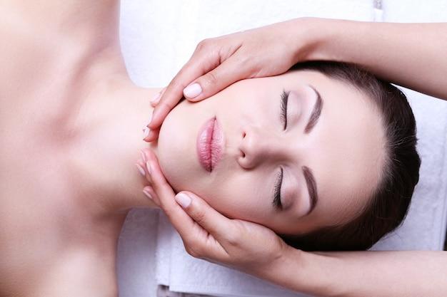Mulher jovem fazendo massagem facial