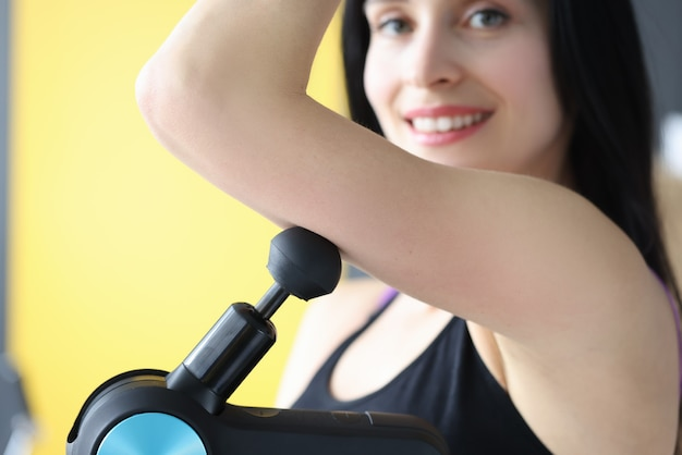 Mulher jovem fazendo massagem muscular no ombro com massageador de percussão closeup